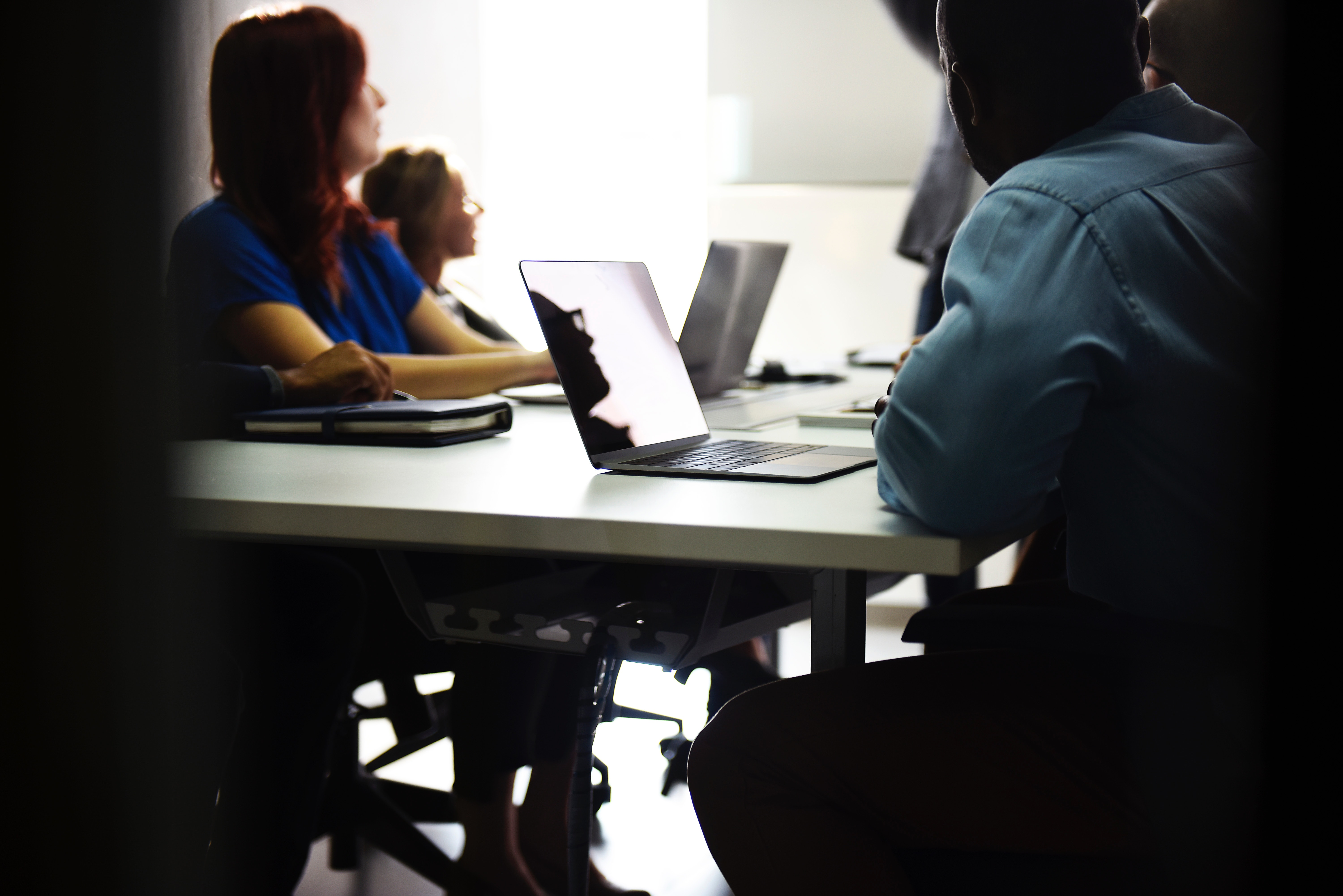 A blurred group on employees sitting at a conference table while diverting their attention to an off-screen presentation speaker.