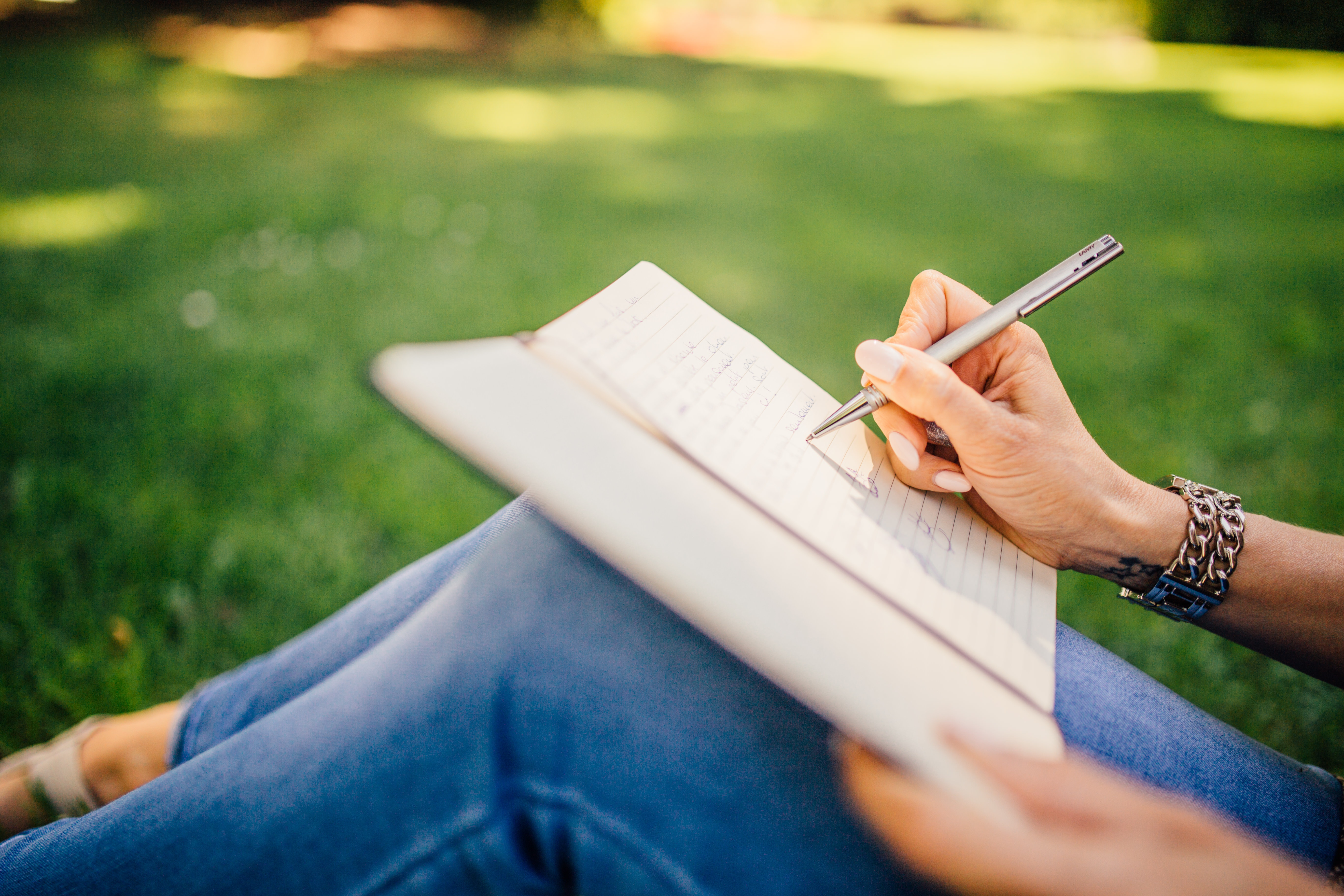 Close up of woman writing in notebook with a metal pen while sitting in the grass.